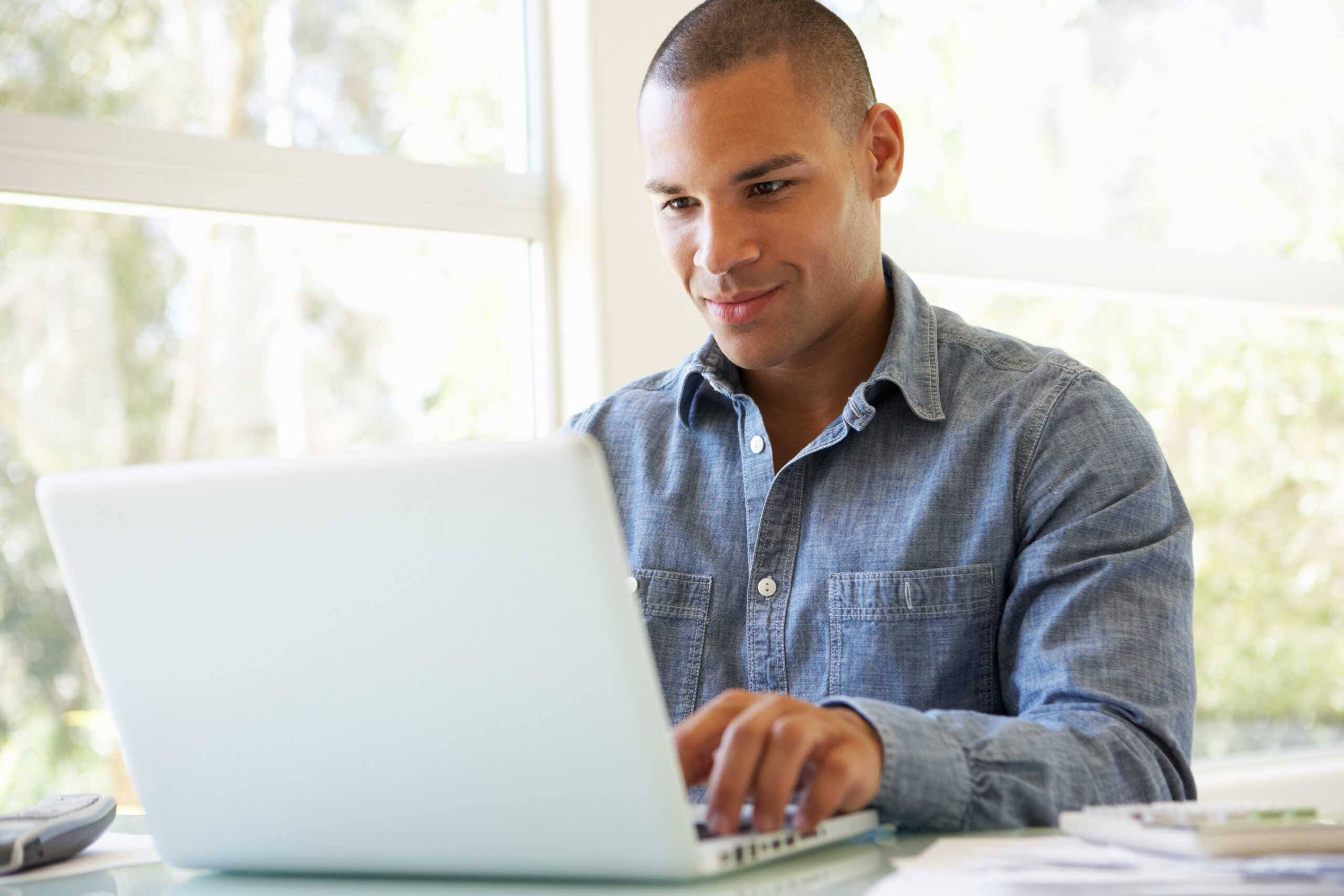 Young Man Using Laptop At Home Looking At The Screen
