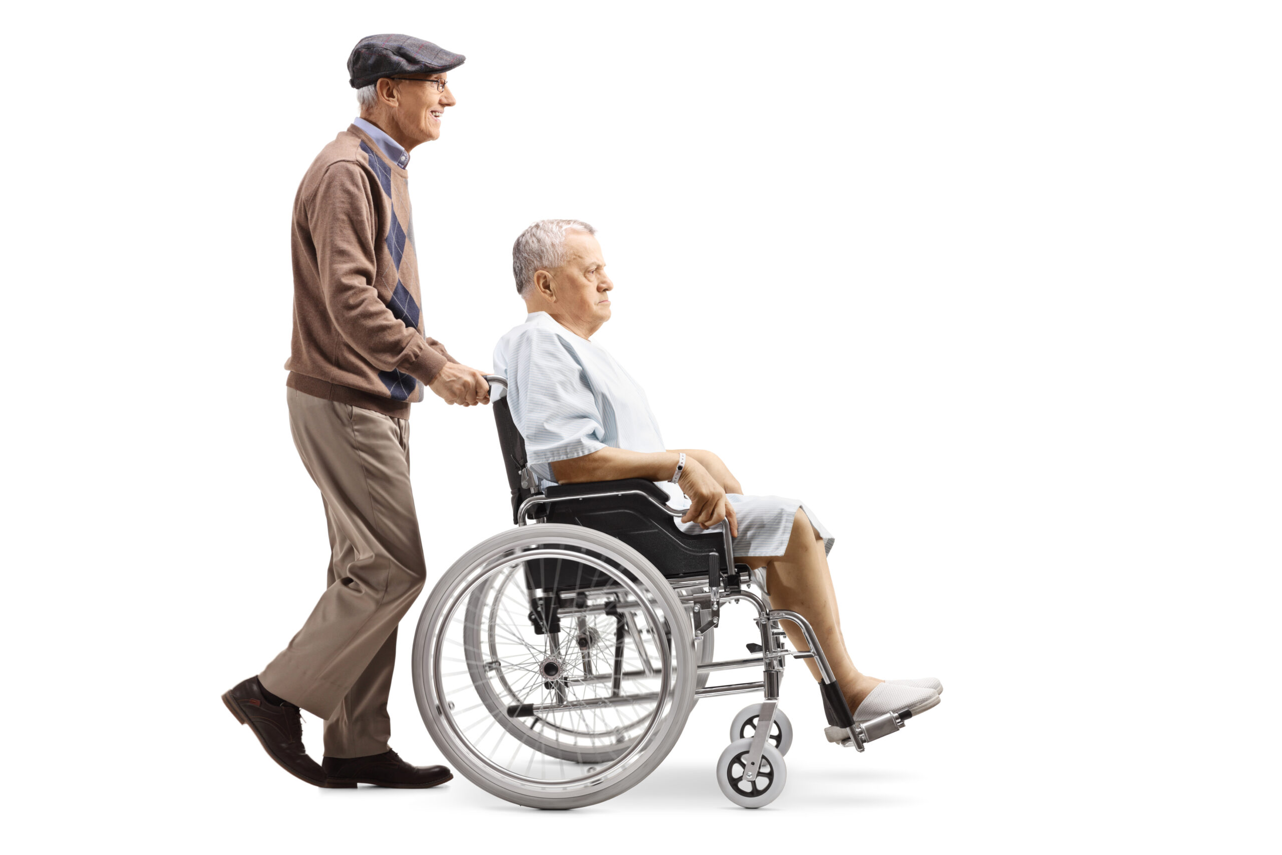Full length profile shot of an elderly man pushing a senior male patient in a wheelchair isolated on white background