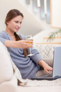 Portrait of a woman having a glass of white wine while using her laptop in her living room